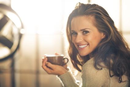 Schönheit zeigt ihr tolles Lächeln und trinkt dabei Kafee