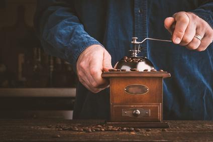 Mann mahlt Kaffeebohnen mit manuell betriebenem Mahlwerk