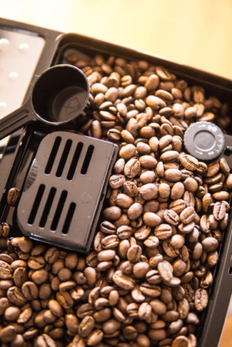 Kaffeebohnen im Kaffeebohnenfach des Kaffeevollautomaten mit Kaffeepulverlöffel.