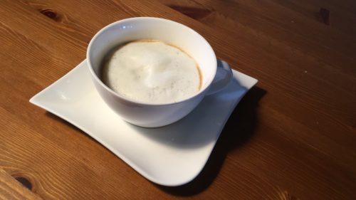 Cappuccino in weißer Tasse auf weißer Untertasse.